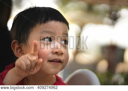 Portrait Of Kid Looking Around And Point Finger Up At Side Of  His Face With Thinking  Idea Space.