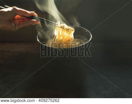Over Light With Hand Woman Clamping Instant Noodles From Black Cup On Black Background. Fast Food An