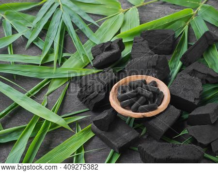 Charcoal Capsule And Charcoal And Leaves On Wood Background.charcoal Capsule For To Cure Diarrhea An