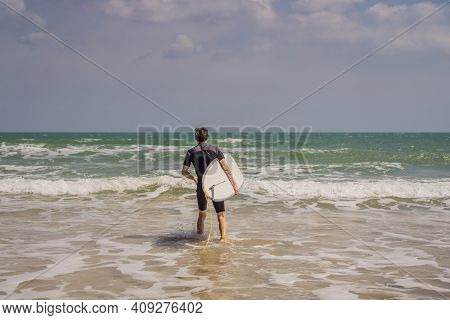Young Surfer Standing Agains The Ocean Looking The Waves, Professional Surfer In Black Wetsuit Holdi