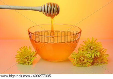 Sweet Floral Honey Pouring From Drizzler In Glass Plate And Flowers Of Dandelion Near, Against Brigh