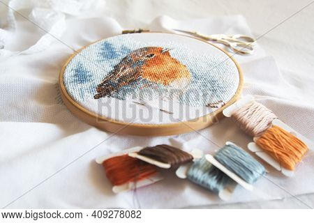 Cross Stitch Process In The Hoop Multicolored Bird, White Canvas, Floss Threads On Bobbins, Needle,