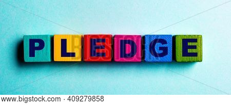 The Word Pledge Is Written On Multicolored Bright Wooden Cubes On A Light Blue Background