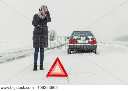 Young Woman Holds Her Head, Stands Near The Triangle Road Warning Sign And Talks On Her Mobile Phone
