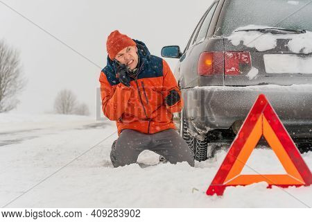 Angry Young Man In An Orange Jacket Is On His Knees Talking On A Mobile Phone On A Snowy Road. He Is
