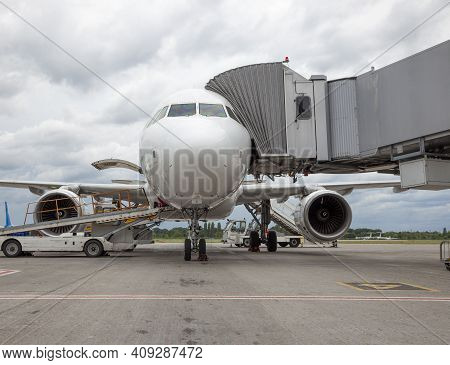 Boarding Passengers On The Plane Through The Boarding Bridge. The Plane Lands At The International A
