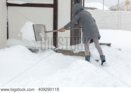 Women Shoveling Snow From The Steps Of His House