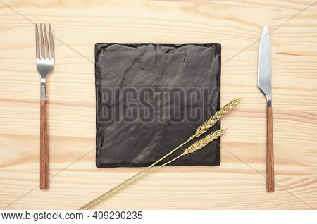 Mockup Blank Plate And Cutlery On Wood Table. Top View Black Recipe Stone Board With Mockup Text Spa