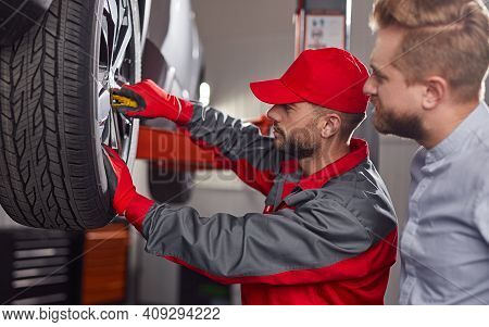 Side View Of Professional Repairman With Wrench Examining Wheel Of Broken Automobile Of Male Client