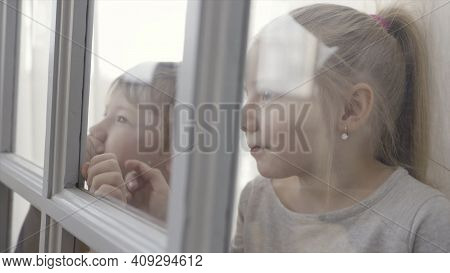 Little Children Boy And Girl Standing Behind The Door With Glass Inserts. Action. Sister And Brother
