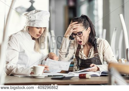 Shock Over Bookkeeping By Female Chef And Restaurant Owner, Sitting Over Paperwork.