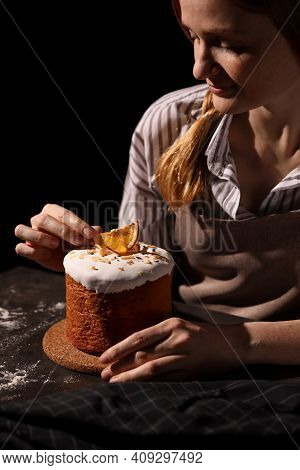 Young Woman Decorating Traditional Easter Cake At Table Against Black Background