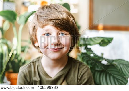 Portrait Of Smiling Child Kid Boy In Green T Shirt With Blue Eyes In Living Room At Sunny Day. Styli