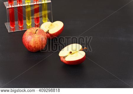 A Red Apple And Laboratory Glass With Red Liquid. How The Fruit Is Colored.