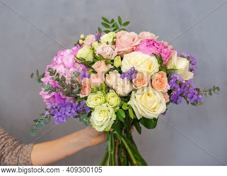Close Up View Of A Beautiful Bouquet Of Mixed Coloful Flowers In A Florist Hand. The Concept Of A Fl