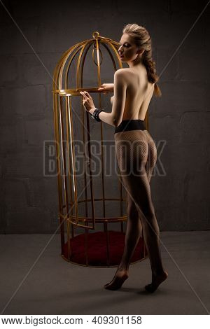 Sexy Topless Woman Standing Near Bdsm Cage