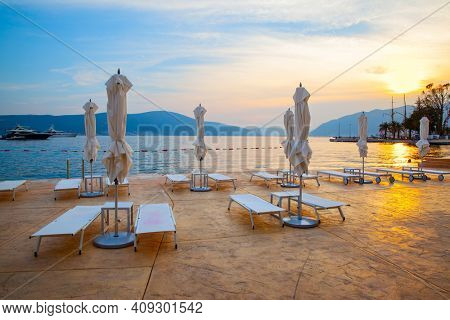 Terrace by the sea with folded parasoles at sunset, Tivat,  Montenegro