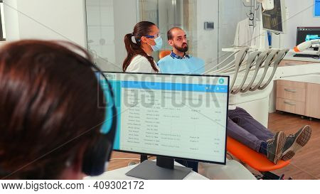 Orthodontist Assistant Making Appointments Using Headset Sitting In Front On Computer While Doctor I
