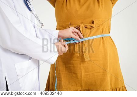 Female Doctor Wearing White Uniform Hold A Tape Measure Around The Waist Of A Obese Woman Wearing A