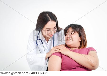 Beautiful Female Doctor Cure Ailments Of Obese Women Patients Asians Seated On A Wheelchair. Obesity