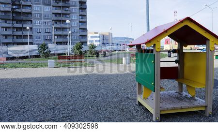 Children's Bright Playhouse On A Playground Covered With Fine Gravel Against The Background Of An Un