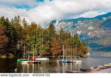 Sailing yachts and motor boats. Bohinj is an alpine lake in the Julian Alps. Slovenia. Magnificent lake with clear water is surrounded by dense forests.