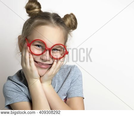 Cute Funny Little Girl With Smiling Facial Emotion Wearing Red Toy Eyeglasses Touching Cheeks Studio