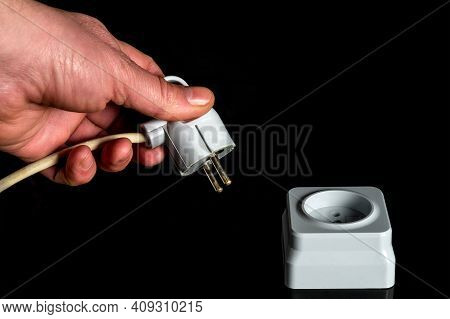 Manually Plug The Power Cord Into A White Plastic Or European Power Outlet. Close Up Of A Man Hand I