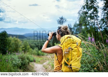 Rear View Of Woman Hiker With Backpack On A Hiking Trip In Nature, Using Binoculars.