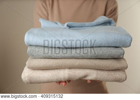 Woman With Folded Cashmere Clothes On Beige Background, Closeup