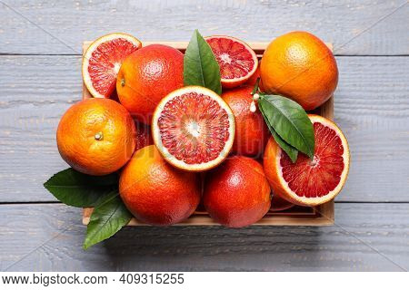 Crate Of Ripe Red Oranges And Green Leaves On Grey Wooden Table, Top View
