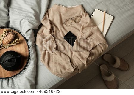 Soft Cashmere Sweater And Tray With Tea Set On Bed At Home