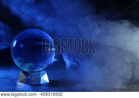 Magic Crystal Ball On Table And Smoke Against Dark Background, Space For Text. Making Predictions
