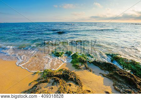 Seascape On A Sunny Morning. Summer Vacation At The Sea. Water Washes Sandy Beach With Rocks. Fluffy