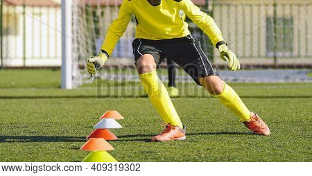 Young Soccer Goalie In Training Action. Boy Soccer Player Improving Speed Skills. Kid Goalkeeper In