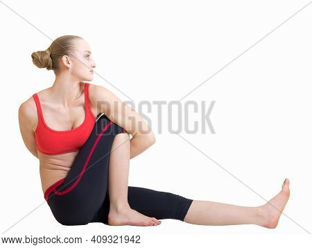 Young Blond Hair Woman In Yoga Pose Bharadvajasana Or Twisting Sage Pose Isolated On White Backgroun