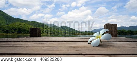 Panoramic View Of White Floral Drop On Wooden Bridge Lake With Green Mountain, Bright Blue Sky And L