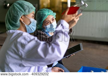 Quality Control Engineer  Work With Female Worker. Workers In The Factory Write Down Notes About Bot