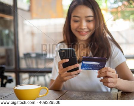 The Smiling Young Asian Woman Enjoys Shopping Online Via A Smartphone And Paying Online Via Credit C
