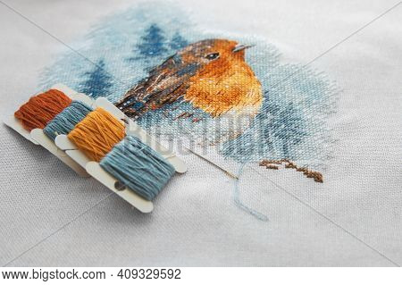 View Of The Cross Stitch Process Multicolored Bird, White Canvas, Floss Threads On Bobbins, Needle,