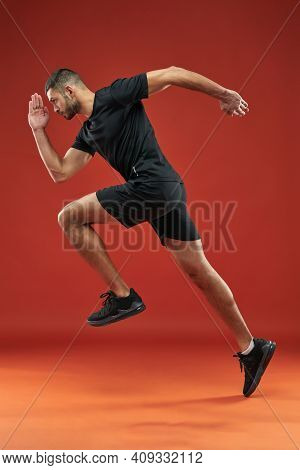 Strong Sportsman In Black Shirt And Shorts Doing Exercises In Sport Club