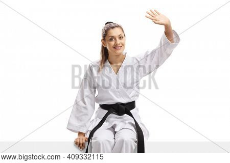 Woman in karate kimono sitting on a panel and waving isolated on white background