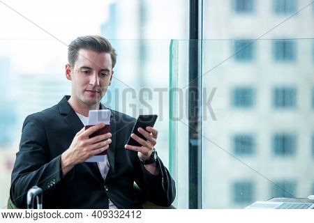 Businessman Holding Passport And  Using Smartphone Check In Air Ticket  And Boarding Card In Departu