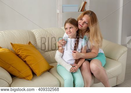 Child With Broken Arm And Gypsum Spend Time At Home With Mother. Childhood Illnesses, A Positive Out