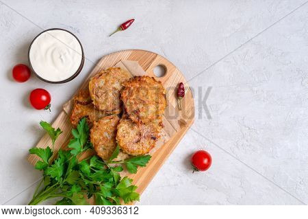 Potato Pancakes With Sour Cream On A Light Background. Vegetarian Dish. Top View. Copy Space