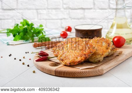 Freshly Cooked Potato Pancakes With Sour Cream On A Wooden Board On The Kitchen Table. Vegetarian Di