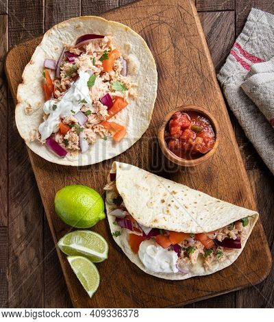 Overhead Of Two Tacos Made With Chicken, Tomato, Onion And Sour Cream With Salsa And Lime On A Woode