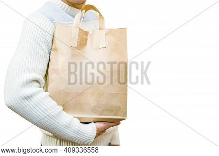 Blank Brown Paper Bag With Handles In Men's Hand In A White Sweater, Isolated On A White Background.