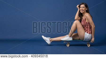 Happy Young Asian Woman Sitting And Holding Surfskate Or Skateboard On Blue Color Background, Exerci