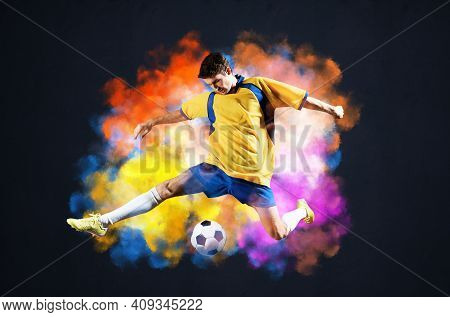 Soccer Player Kicking Ball In Colorful Smoke. Sportsman In Yellow And Blue Uniform In Action. Soccer